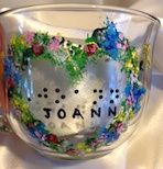 Glass mug 14oz. with Heartshape garland of various color flowers. In center has name in braille and script