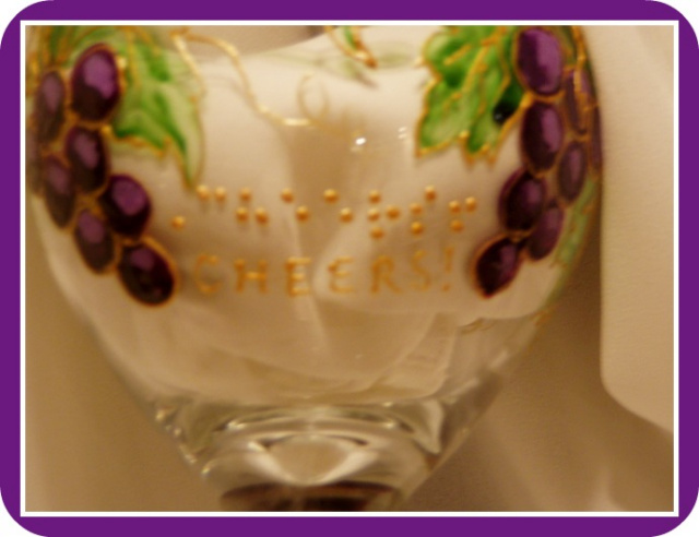 18 ounce wine glass. Design is purple grape clusters with green leaves, outlined in raised gold outlining. The word Cheers in braille and script