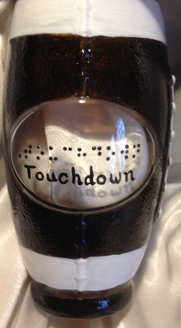 """Touchdown"" and ""Game Time"" in raised-dot braille and script on two sides of this unique football-shaped glass!  Painted dark brown and accented with white stripes and lacing."