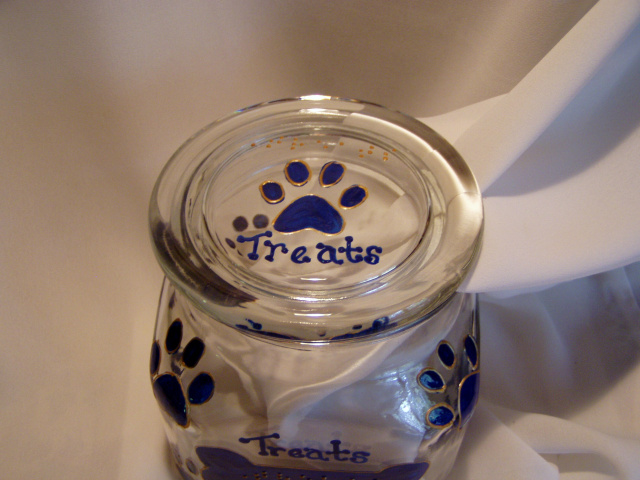"Jars are glass, square 1qt. size, with plastic seal on inside of lid to ensure freshness. The lid has a pawprint and the word ""treats"" in raised dot braille above the pawprint, and in script below the pawprint.  The pawprint design is outlined so the design can be felt all the way around the jar.  The front of the jar has a dog bone shape (also outlined) with the word ""Treats"" in raised dot braille."