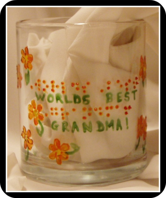 Coffee Mug- with orange flowers and green leaves.  Words are Worlds Best Grandma in braille and script